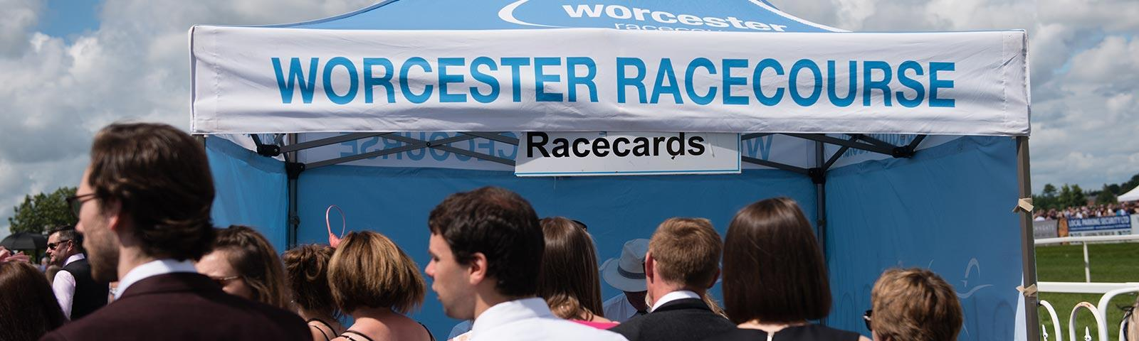 Crowds standing in front of a tent at Worcester Racecourse, waiting to buy racecards.