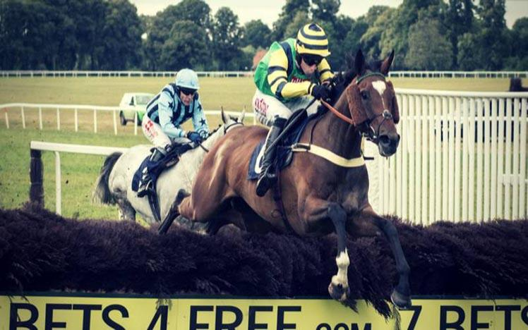 Two runners jumping a fence at Worcester Racecourse