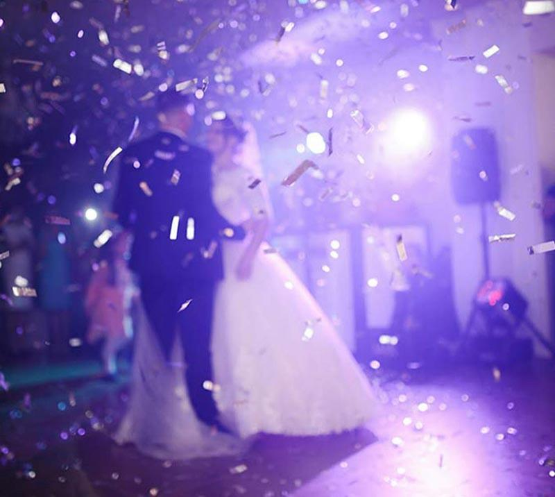 A bride and groom enjoy their first dance as confetti is thrown around them.