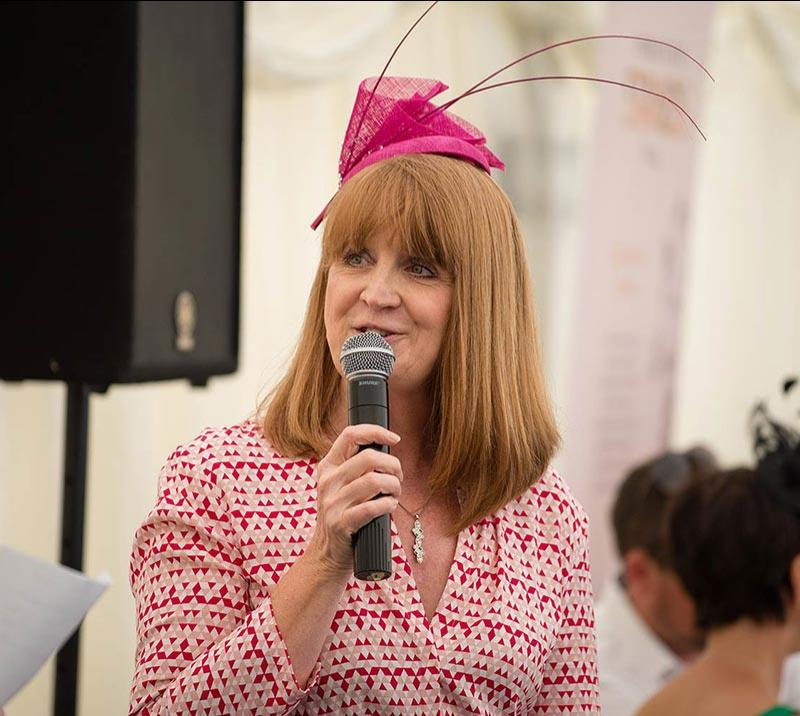 A well dressed Lady gives a speech whilst holding a microphone close to her mouth.