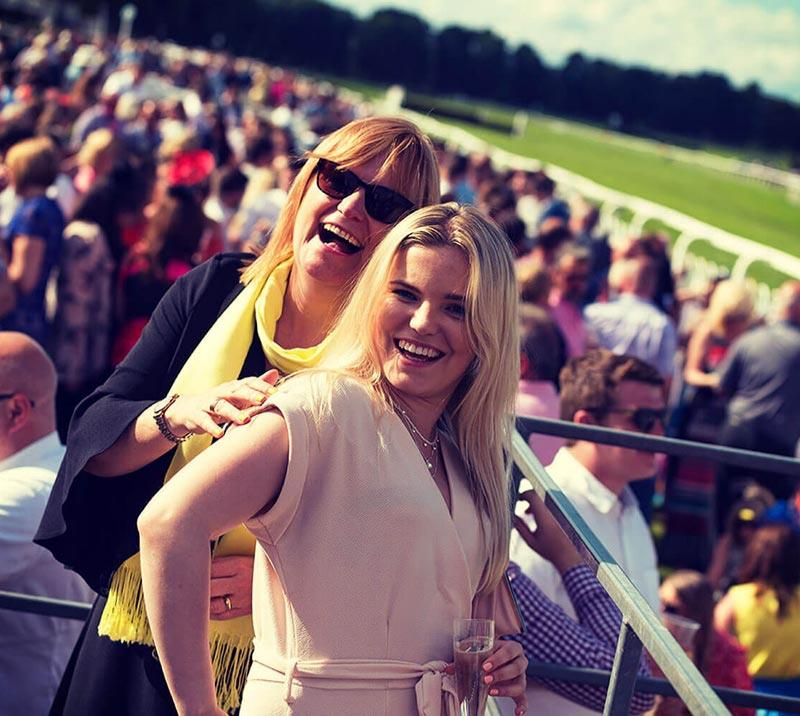 Two women posing for a photo at Worcester Racecourse with crowds in the background.